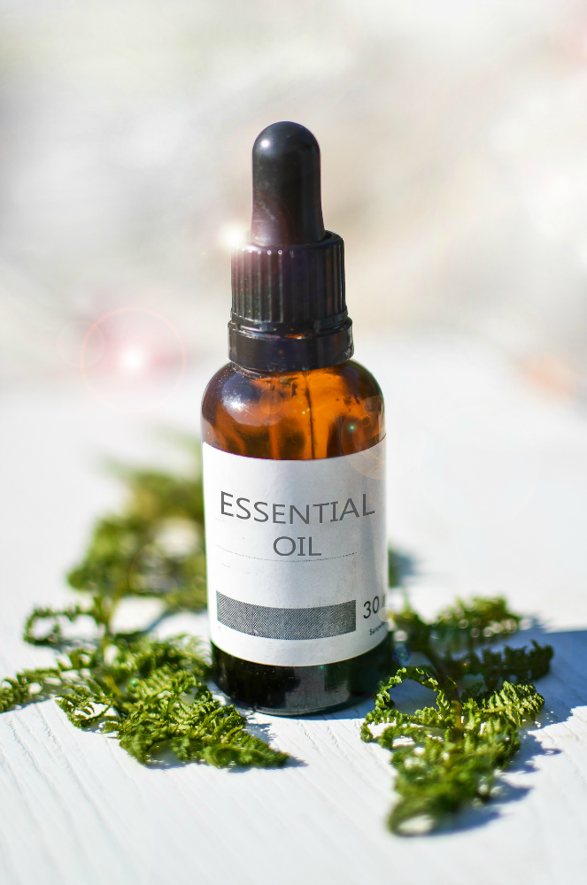 essential oil botle with herbs around it essential oils for depression, insomnia, and anxiety