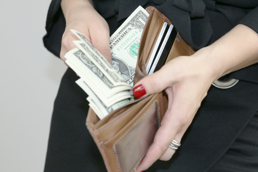 women holding wallet with money