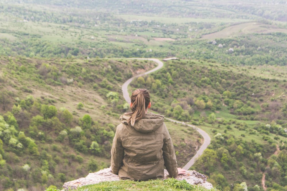 woman sitting on a cliff looking out over a road in the distance living a purpose driven life being goal oriented