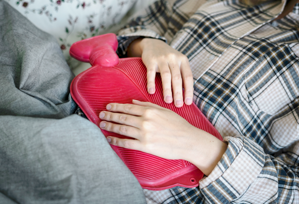 woman with hot water bottle on her abdomin what are normal menstrual symptoms living with endometriosis
