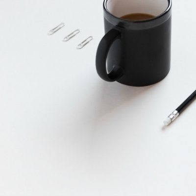 items lined up perfectly on a white desk overcome procrastination caused by perfectionism